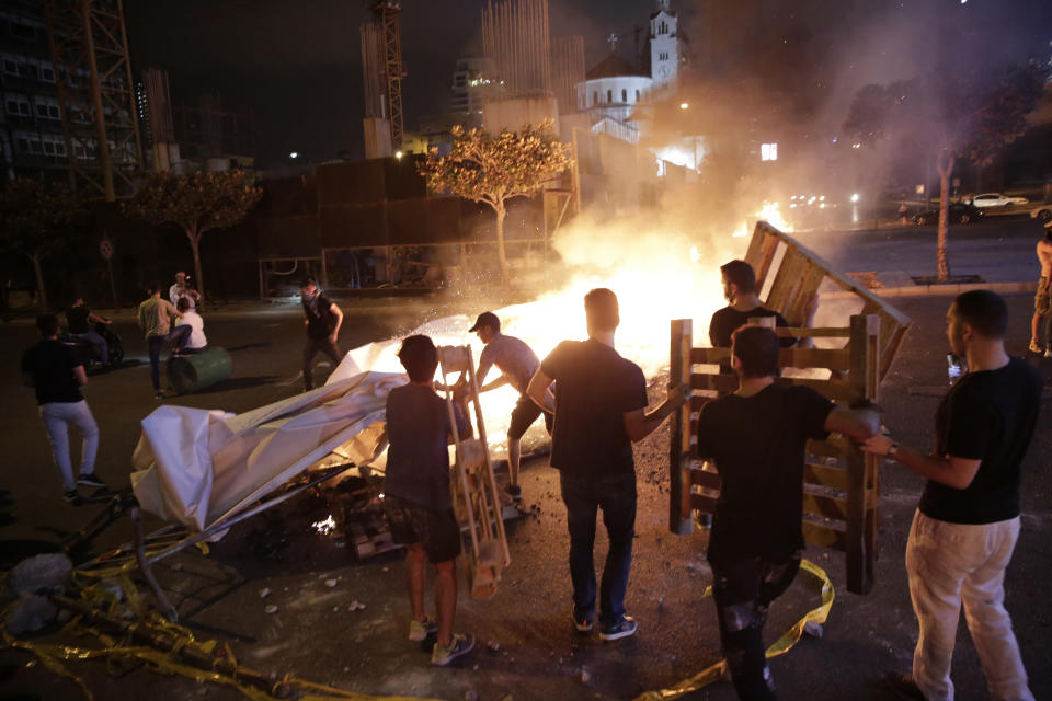 An anti-government protester sets fire to plastic barriers and trash to block a road during a demonstration in Beirut, Lebanon, Thursday, Oct. 17, 2019. Scores of people are protesting in Beirut and other parts of Lebanon over the government's plans to impose new taxes amid a harsh economic crisis in the country. (AP Photo/Hassan Ammar)