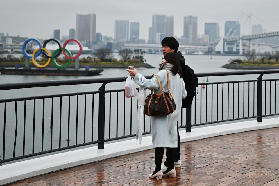 A couple stands before the Olympic Rings at Odaiba Seaside Park in Tokyo on March 8, 2020.