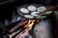 The daughter of Gonzalo Ramirez cooks tortillas at their home, in La Palmilla