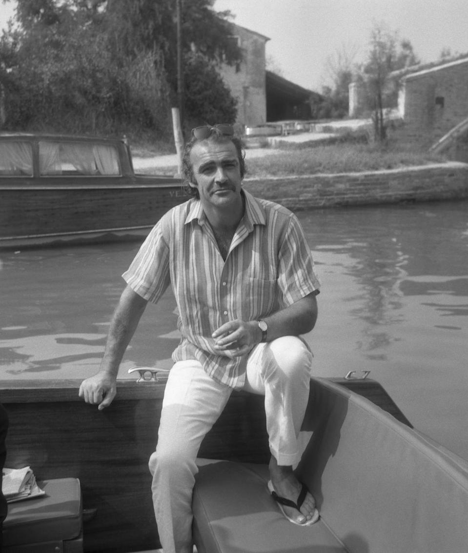 <p>Connery, wearing a striped short sleeves shirt, linen trousers, slippers and sunglasses, sitting on a water taxi with Torcello Island on the background, Venice, circa 1970. </p>