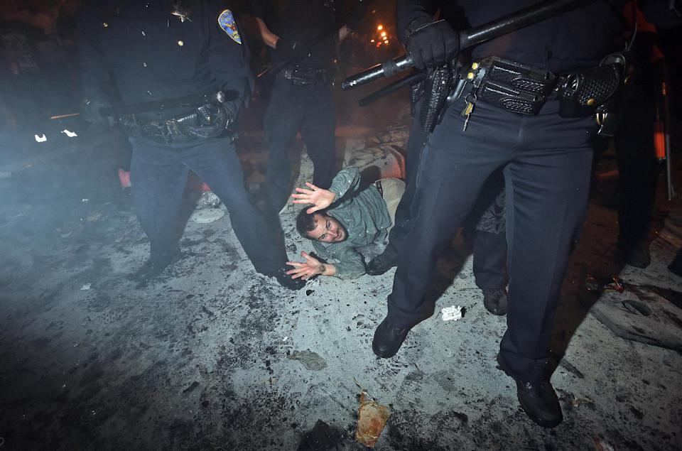 San Francisco police officers subdue a man who was seen driving a meter maid vehicle through the Mission district after the San Francisco Giants won the World Series baseball game against the Kansas City Royals on Wednesday, Oct. 29, 2014, in San Francisco. There were several reports of fires being set and violence breaking out after the Giants win. (AP Photo/Noah Berger)
