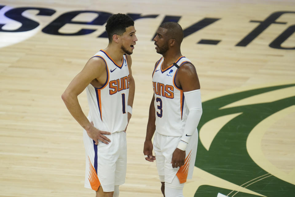 Phoenix Suns' Chris Paul (3) talks with Devin Booker (1) during the first half of Game 3 of basketball's NBA Finals against the Milwaukee Bucks, in Milwaukee, Sunday, July 11, 2021. (AP Photo/Paul Sancya)