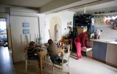 Members of the Israeli Ziv family are seen in their kitchen in the Jewish settler outpost of Amona in the West Bank, November 22, 2016.  REUTERS/Ronen Zvulun