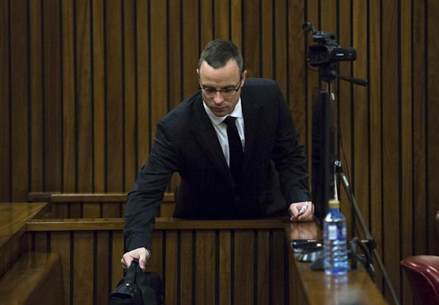 Oscar Pistorius puts his bag upon his arrival at a courtroom for his ongoing murder trial at the high court in Pretoria, South Africa, Tuesday, May 13, 2014. Pistorius is charged with the shooting death of his girlfriend Reeva Steenkamp on Valentine's Day in 2013. (AP Photo/Daniel Born, Pool)
