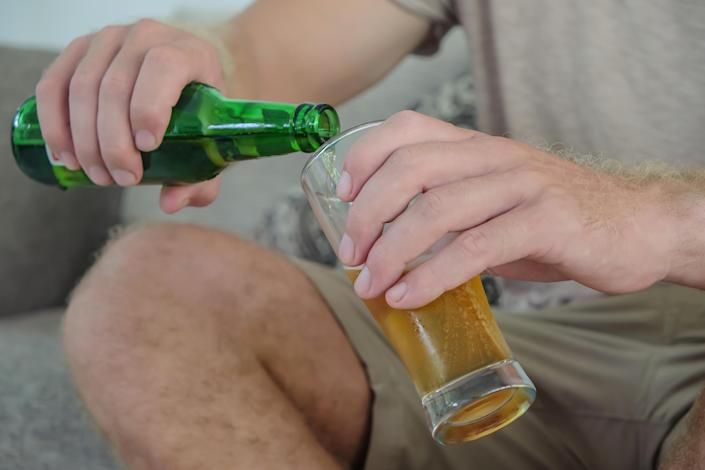 Cropped shot of an unrecognizable young man pouring a cold bottle of beer while sitting on sofa