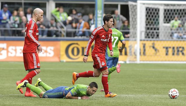 Seattle Sounders's Clint Dempsey, second from left, goes down after battling with Toronto FC's Michael Bradley, left, and Alvaro Rey, right, for the ball in the first half of an MLS soccer match on Saturday, March 15, 2014, in Seattle. (AP Photo/Ted S. Warren)