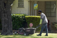 A gardener mows a lawn at a home in Sacramento, Calif., Wednesday, Oct. 13, 2021. Gov. Gavin Newsom signed 92% of the new laws lawmakers sent to him at the end of the years legislative session that ended Sept. 10. One of the bills approved clears the way for a first-ever ban on the sale of new gas-powered leaf blowers and lawn blowers. (AP Photo/Rich Pedroncelli)
