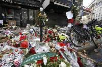 Candles, flowers and messages pay tribute to victims in front of the La Belle Equipe cafe, one of the sites of the deadly attacks in Paris, France, November 17, 2015. REUTERS/Jacky Naegelen