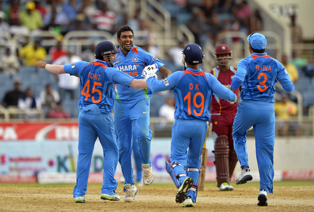 Indian bowler Ravichandran Ashwin (2nd L) celebrates with teammates after bowling out West Indies batsman Denesh Ramdin during the second match of the Tri-Nation series between Indian and West Indies at the Sabina Park stadium in Kingston on June 30, 2013. India have scored 229/7 at the end of their innings. AFP PHOTO/Jewel Samad        (Photo credit should read JEWEL SAMAD/AFP/Getty Images)