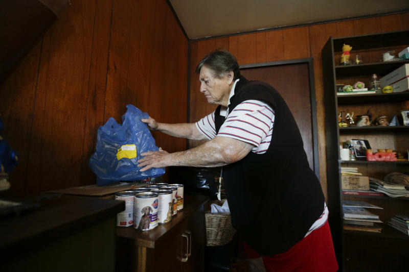In this Dec. 10, 2013 image, Sherry Scott sorts through the cans of dog food she received through the Animeals program at her home in San Diego. Scott said she would give her lasagne and pork riblets from Meals on Wheels to her 10-year-old golden retriever if MOW didn't bring dog food for the dog. The pet food program is sponsored by the Helen Woodward Animal Center. (AP Photo/Gregory Bull)