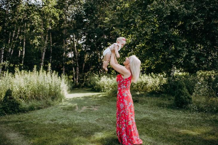 Shelby Beck holds her daughter up in the air