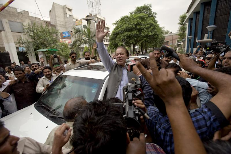 Former Prime Minister and leader of the Pakistan Muslim League, Nawaz Sharif, center, waves to his supporters as he leaves a polling station after casting his vote in Lahore, Pakistan, Saturday, May 11, 2013. Defying the danger of militant attacks, Pakistanis streamed to the polls Saturday for a historic vote pitting a former cricket star against a two-time prime minister and an unpopular incumbent. But attacks that killed several people and wounded dozens more underlined the risks many people took just casting their ballots. (AP Photo/Anjum Naveed)