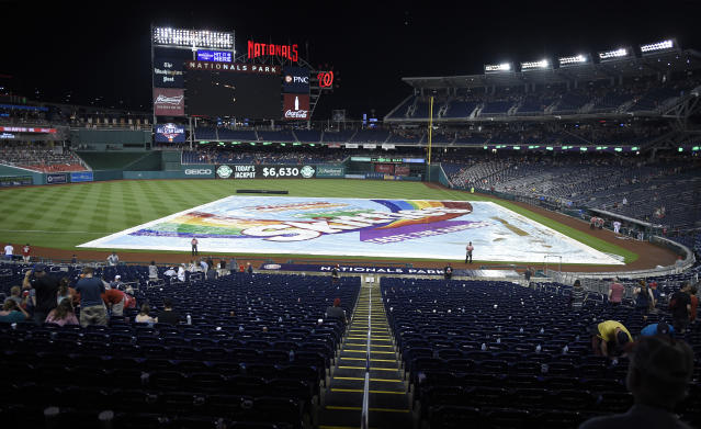 The tarp covers the field during a rain delay in the fourth inning of a baseball game between the Washington Nationals and the Philadelphia Phillies, Sunday, June 24, 2018, in Washington. (AP Photo/Nick Wass)