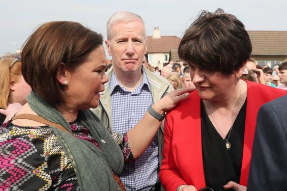 Mary Lou McDonald and Arlene Foster in Creggan on Friday evening (PA)