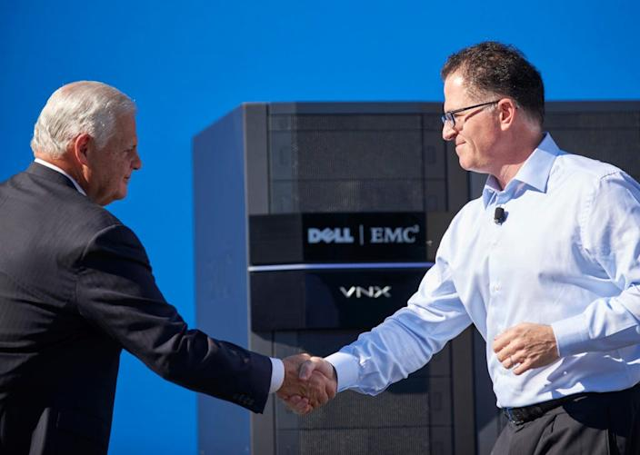 EMC CEO Joe Tucci (left) shakes hands with Dell CEO and founder Michael Dell (right).