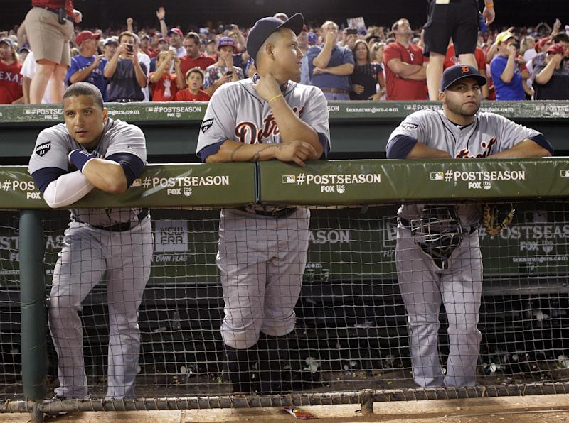 From left, Detroit Tigers Victor Martinez, Miguel Cabrera and Omir Santos watch as the Texas Rangers celebrate winning Game 6 of baseball's American League championship series against the Detroit Tigers 15-5, Saturday, Oct. 15, 2011, in Arlington, Texas. Texas moves on to the world series.  (AP Photo/Paul Sancya)