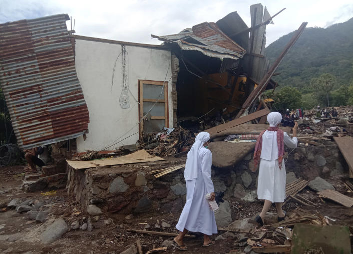 Nuns walk past a damaged house at a flood-affected village in Ile Ape on Lembata Island, East Nusa Tenggara province, Indonesia, Tuesday, April 6, 2021. Rescuers in remote eastern Indonesia were digging through the debris of a landslide Tuesday in search of people believed to be buried in one of several disasters brought on by severe weather in the Southeast Asian nation and neighboring East Timor. (AP Photo/Ricko Wawo)
