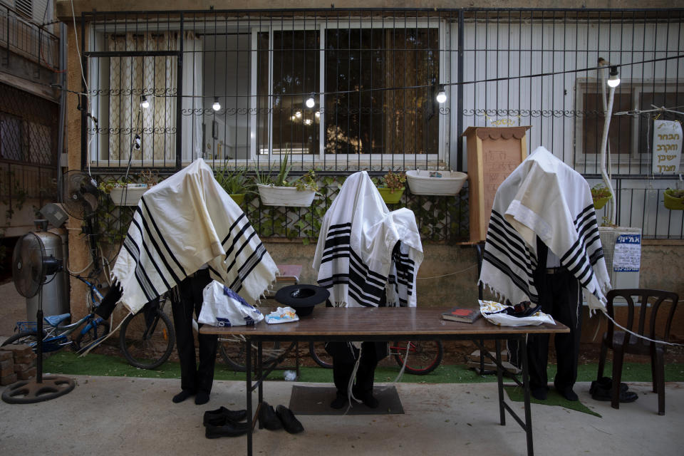 Ultra-Orthodox Jews pray covered in prayer shawls in divided sections which allow a maximum of twenty worshipers, next to their house as synagogues are closed following government measures to help stop the spread of the coronavirus, in Bnei Brak, Israel, Sunday, Oct. 18, 2020. (AP Photo/Oded Balilty)