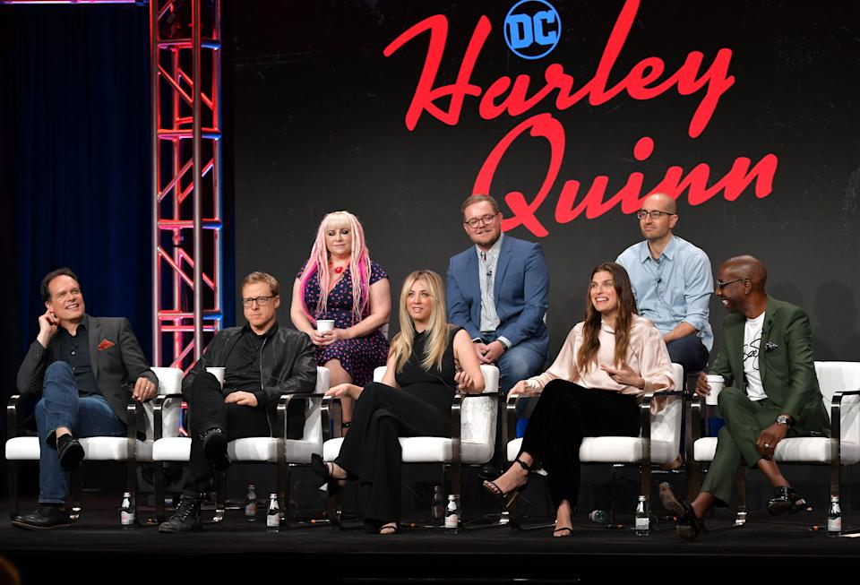 "BEVERLY HILLS, CALIFORNIA - JULY 23: (L-R) Diedrich Bader, Alan Tudyk, Jennifer Coyle, Kaley Cuoco, Patrick Schumacker, Lake Bell, Justin Halpern, and J.B. Smoove from ""Harley Quinn"" speak onstage at the DC Universe panel during the 2019 Summer TCA Press Tour at The Beverly Hilton Hotel on July 23, 2019 in Beverly Hills, California. (Photo by Amy Sussman/Getty Images)"