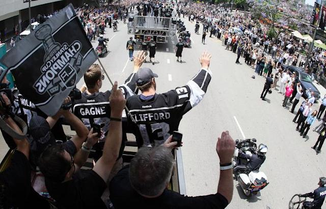 LOS ANGELES, CA - JUNE 14: Simon Gagne #12 and Kyle Clifford #13 of the Los Angeles Kings waves to fans during the Los Angeles Kings Stanley Cup Victory Parade on June 14, 2012 in Los Angeles, California. (Photo by Victor Decolongon/Getty Images)
