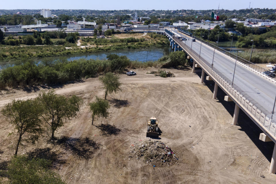 A bulldozer is seen next to a mound of debris while crews clear an area where migrants, many from Haiti, were encamped along the Del Rio International Bridge, Friday, Sept. 24, 2021, in Del Rio, Texas. (AP Photo/Julio Cortez)