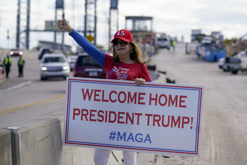 A supporter of President Donald Trump waits for the motorcade on the road to Mar-a-Lago, Trump's Palm Beach estate, on Wednesday, Jan. 20, 2021, in West Palm Beach, Fla. (AP Photo/Lynne Sladky)