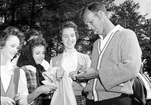 Always popular with the young female fans, Palmer signs autographs at the 1961 Masters.