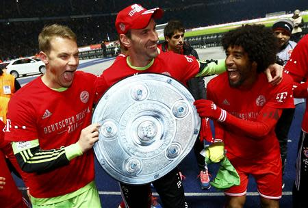 Bayern Munich's goalkeepers Manuel Neuer and Tom Starke (C) hold a mock German soccer championship trophy with Dante (R) as they celebrate winning the Bundesliga title after the German first division Bundesliga soccer match against Hertha Berlin, in Berlin March 25, 2014. REUTERS/Kai Pfaffenbach