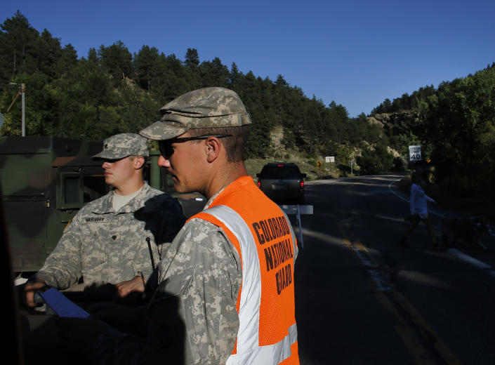 National Guard soldiers man a checkpoint on a closed canyon road, which is washed out in places by recent flooding, up Boulder Canyon, west of Boulder, Colo., Friday Sept. 20, 2013. With snow already dusting Colorado's highest peaks, the state is scrambling to replace key mountain highways washed away by flooding. More than 200 miles of state highways and at least 50 bridges were damaged or destroyed, not counting many more county roads. (AP Photo/Brennan Linsley)
