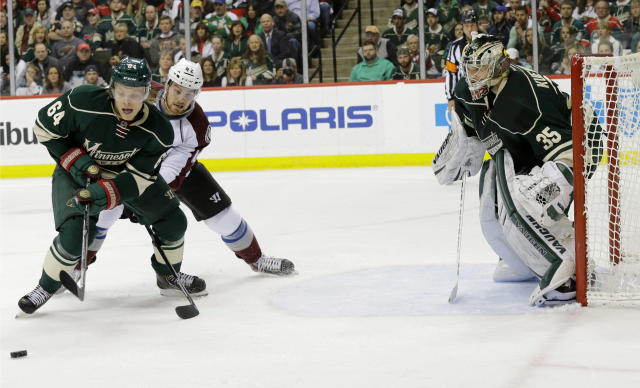 Minnesota Wild center Mikael Granlund (64), of Finland, controls the puck in front of Colorado Avalanche center Brad Malone (42) as Wild goalie Darcy Kuemper (35) covers the net during the second period of Game 6 of an NHL hockey first-round playoff series in St. Paul, Minn., Monday, April 28, 2014. The Wild won 5-2. (AP Photo/Ann Heisenfelt)