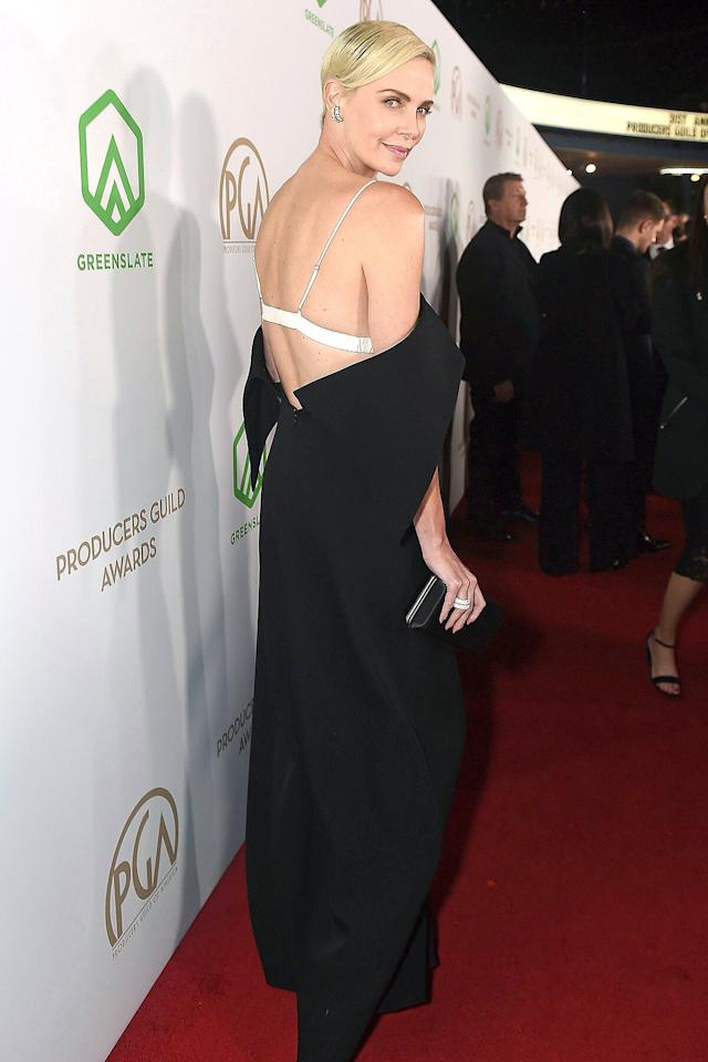 in an off-the-shoulder black gown with a white triangle bra peeking out underneath at the Producers Guild of America Awards.