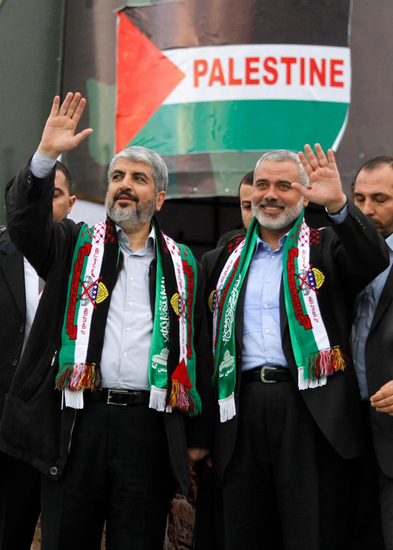 In this Dec. 8, 2012 file photo, Hamas chief Khaled Mashaal, left, and Hamas and Prime Minister Ismail Haniyeh wave to Palestinian Hamas supporters during a rally to commemorate the 25th anniversary of the Hamas militant group, in Gaza city - Credit: AP