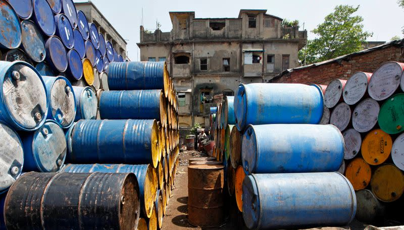 A labourer works amid oil containers at a wholesale fuel market in Kolkata