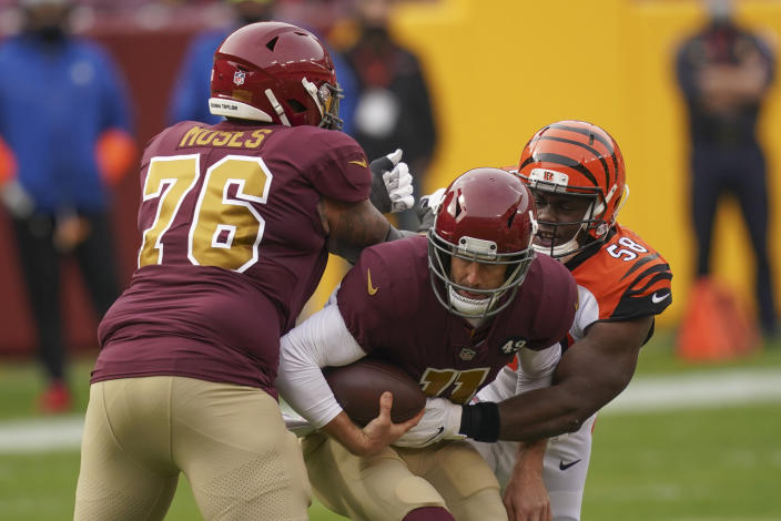 Washington Football Team quarterback Alex Smith (11) is sacked by Cincinnati Bengals defensive end Carl Lawson (58) during the first half of an NFL football game, Sunday, Nov. 22, 2020, in Landover. Trying to stop Lawson is Washington Football Team offensive tackle Morgan Moses (76). (AP Photo/Andrew Harnik)