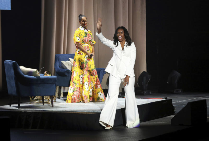 """Former first lady Michelle Obama greets the audience as Tracee Ellis Ross watches at the """"Becoming: An Intimate Conversation with Michelle Obama"""" event at the Forum on Thursday, Nov. 15, 2018, in Inglewood, Calif. (Photo by Willy Sanjuan/Invision/AP)"""