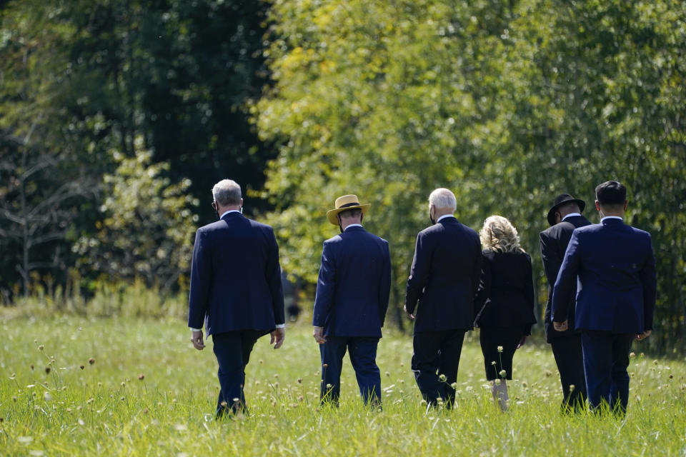 President Joe Biden and first lady Jill Biden walk with Gordon Felt, brother of Edward Porter Felt and President of Families for Flight 93, second from left, and Calvin Wilson the brother-in-law of First Officer LeRoy Homer, a passenger on Flight 93, second from right, to visit a boulder marking the impact site of Flight 93 at the Flight 93 National Memorial in Shanksville, Pa., Saturday, Sept. 11, 2021. The Bidens visited to commemorate the 20th anniversary of the Sept. 11, 2001, terrorist attacks. (AP Photo/Evan Vucci)