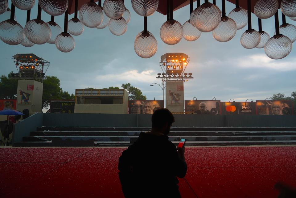 A worker uses his phone to scan hailstones on the red carpet of the 78th edition of the Venice Film Festival at the Venice Lido, Italy, Monday, Aug. 30, 2021. The festival opens Sept. 1 through Sept. 11. (AP Photo/Domenico Stinellis)