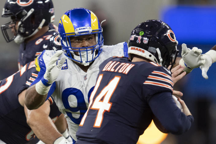 FILE- In this Sunday, Sept. 12, 2021, file photo, Los Angeles Rams defensive end Aaron Donald (99) tackles Chicago Bears quarterback Andy Dalton (14) during an NFL football game in Inglewood, Calif. As Donald, now 30, closes in on the franchise's career sacks record this week, the three-time NFL Defensive Player of the Year says the only difference in his game with age is the recovery time necessary for minor injuries. (AP Photo/Kyusung Gong, File)