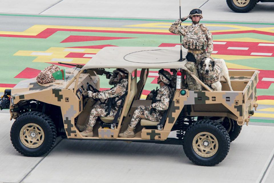 Turkmenistan's army soldiers ride a buggy during a military parade celebrating the country's 30th independence anniversary in Ashgabat, Turkmenistan, Monday, Sept. 27, 2021. The pomp-filled parade took place in Ashgabat, the capital of the gas-rich former Soviet nation in Central Asia. Aside from troops and military equipment, the parade featured employees of state ministries and institutions demonstrating their achievements and Alabai dogs, which accompanied soldiers on military vehicles. (AP Photo/Alexander Vershinin)