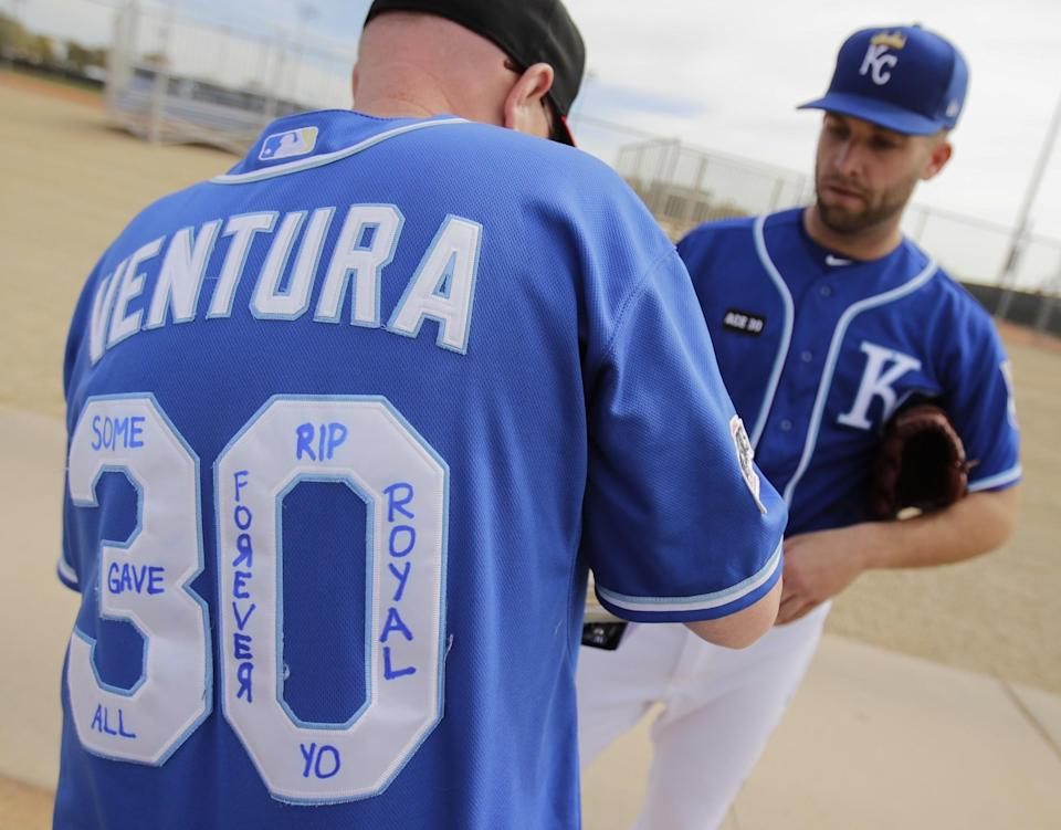 Royals pitcher Danny Duffy (right) talks to a fan wearing a jersey in memory of Yordano Ventura. (AP)