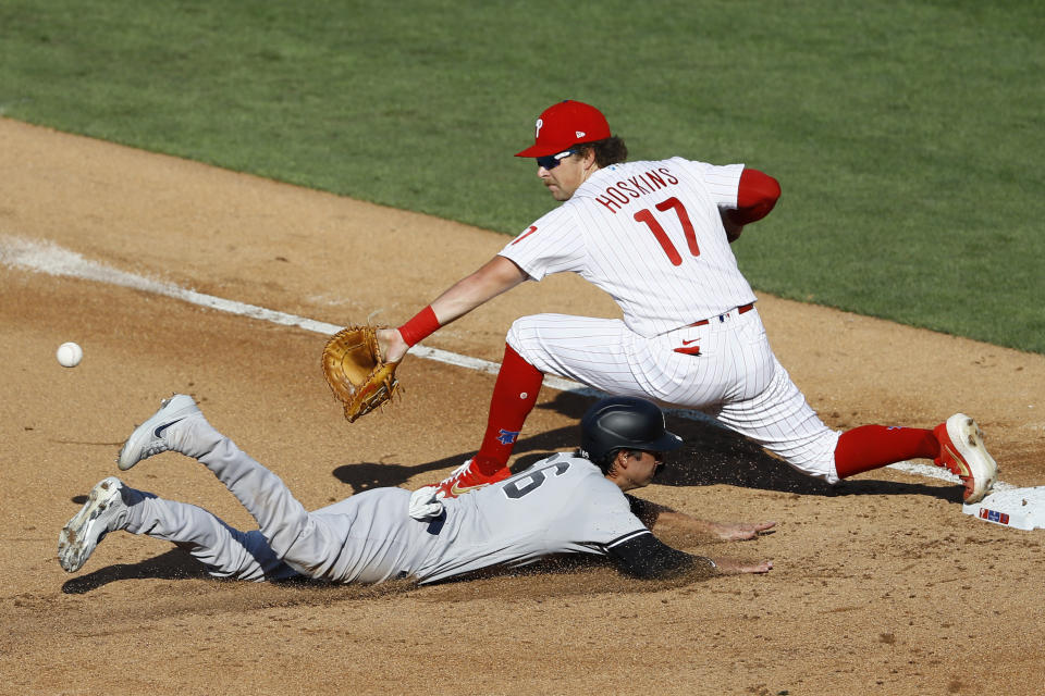 New York Yankees' Kyle Higashioka, bottom, is forced out at first by Philadelphia Phillies first baseman Rhys Hoskins after a popout by Brett Gardner during the fourth inning of the first baseball game in doubleheader, Wednesday, Aug. 5, 2020, in Philadelphia. (AP Photo/Matt Slocum)