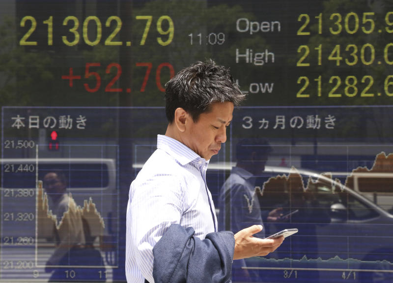 A man walks by an electronic stock board of a securities firm in Tokyo, Monday, May 20, 2019. Shares are mixed in Asia, with India and Australia leading gains following elections that look set to keep incumbents in office.(AP Photo/Koji Sasahara)