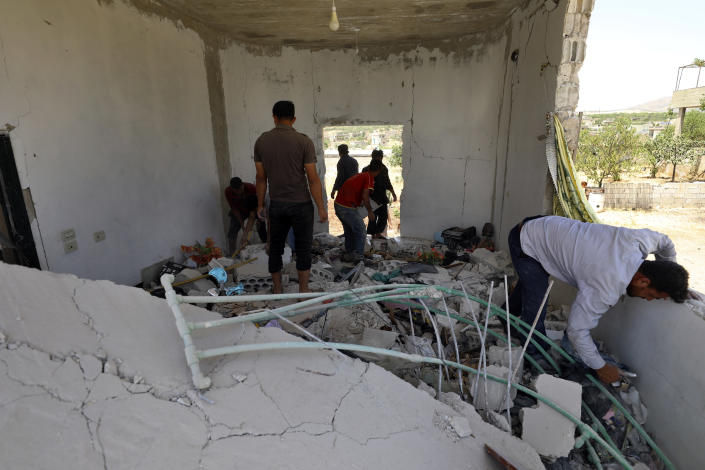 People inspect a damage house after shelling hit the town of Ibleen, a village in southern Idlib province, Syria, Saturday, July 3, 2021. Artillery fire from government-controlled territory Saturday killed at least eight civilians in Syria's last rebel enclave, most of them children, rescue workers and a war monitor said. (AP Photo/Ghaith Alsayed)
