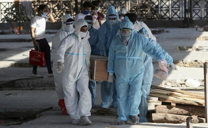 Health workers and relatives carry a body.