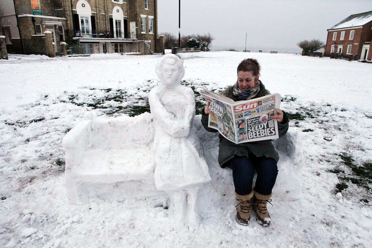A woman sits next to a snowlady while reading a newspaper in Southwold, Suffolk (Rex Features)