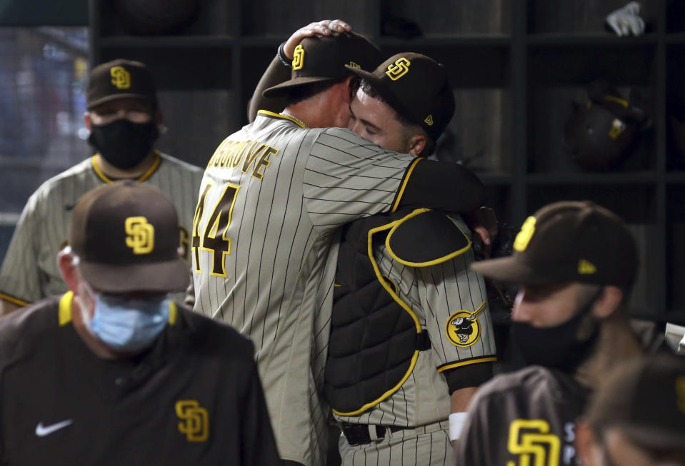 San Diego Padres starting pitcher Joe Musgrove (44) hugs catcher Victor Caratini (17) in the dugout after pitching a no-hitter against the Texas Rangers in a baseball game Friday, April 9, 2021, in Arlington, Texas. (AP Photo/Richard W. Rodriguez)