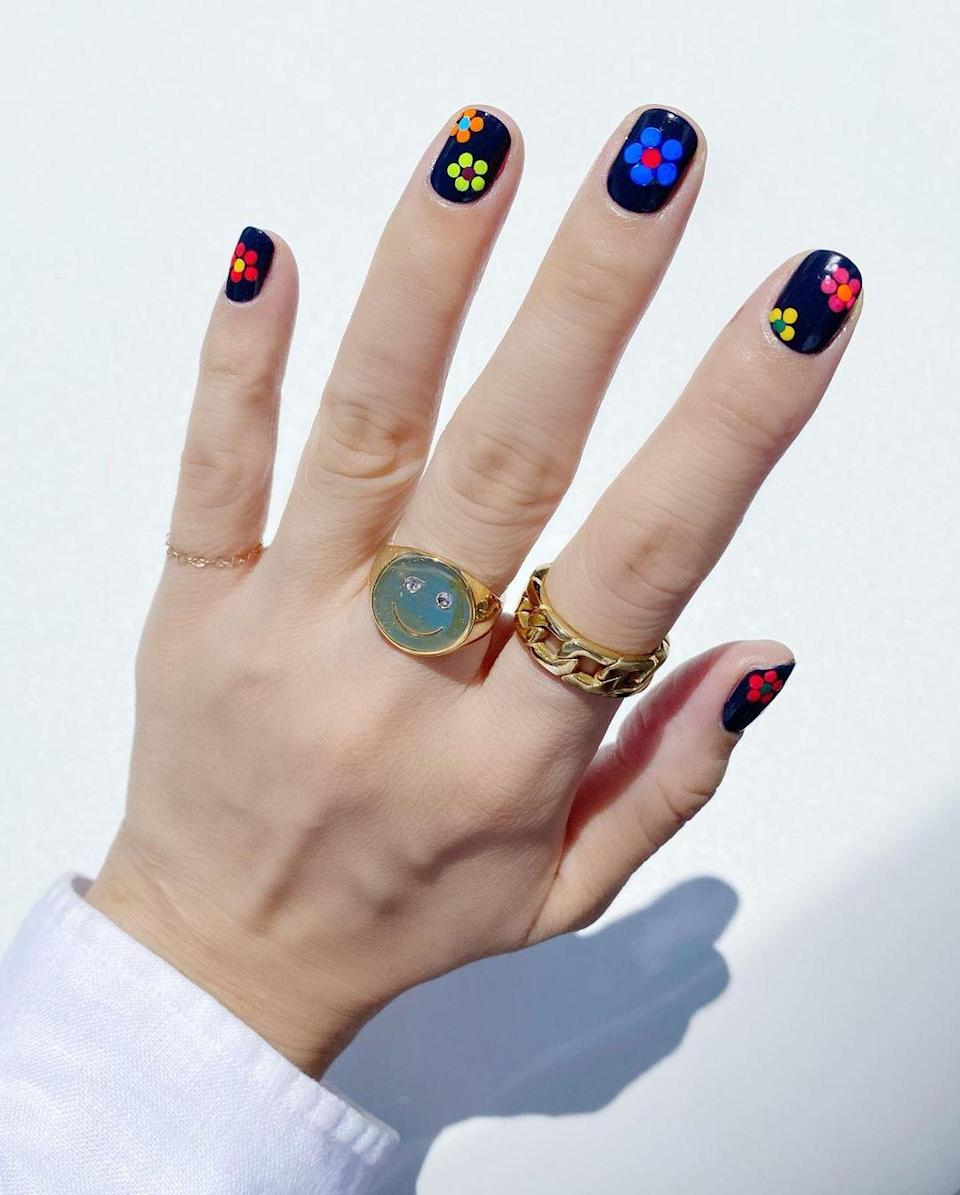 Vivid colors on a dark background makes for a mani no one will forget. The best part of this one is it's a basic daisy, so it's low effort-minimal impact.