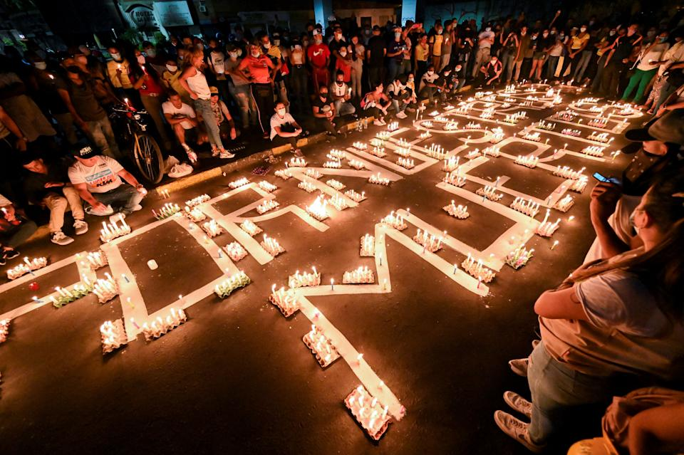 People gather around candles and words on the pavement reading