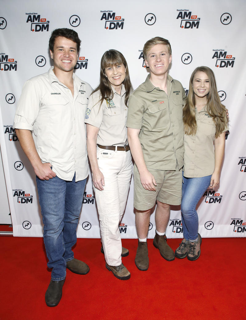 Chandler Powell, Terri Irwin, Robert Irwin and Bindi Irwin pose in front of a media wall wearing khaki clothes