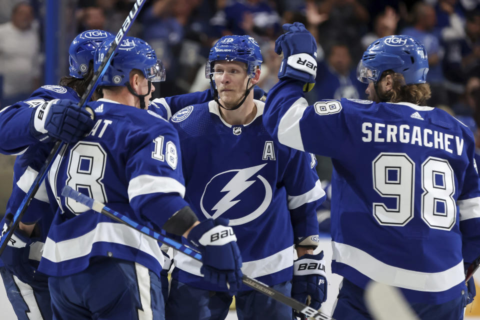 Tampa Bay Lightning's Ondrej Palat (18) and Mikhail Sergachev (98) congratulate Corey Perry (10) after his goal against the Carolina Hurricanes during the second period of a preseason NHL hockey game Friday, Oct. 1, 2021, in Tampa, Fla. (AP Photo/Mike Carlson)
